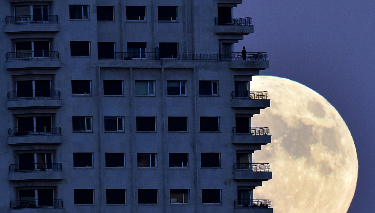 "A man stands on a balcony of a building of Madrid as the moon rises in background, on November 13, 2016, on the eve of a ""supermoon"". On November 14, 2016, the moon will orbit closer to the earth than at any time since 1948, named a 'supermoon', it is defined by a Full or New moon coinciding with the moon's closest approach to the Earth. / AFP / GERARD JULIEN (Photo credit should read GERARD JULIEN/AFP/Getty Images)"
