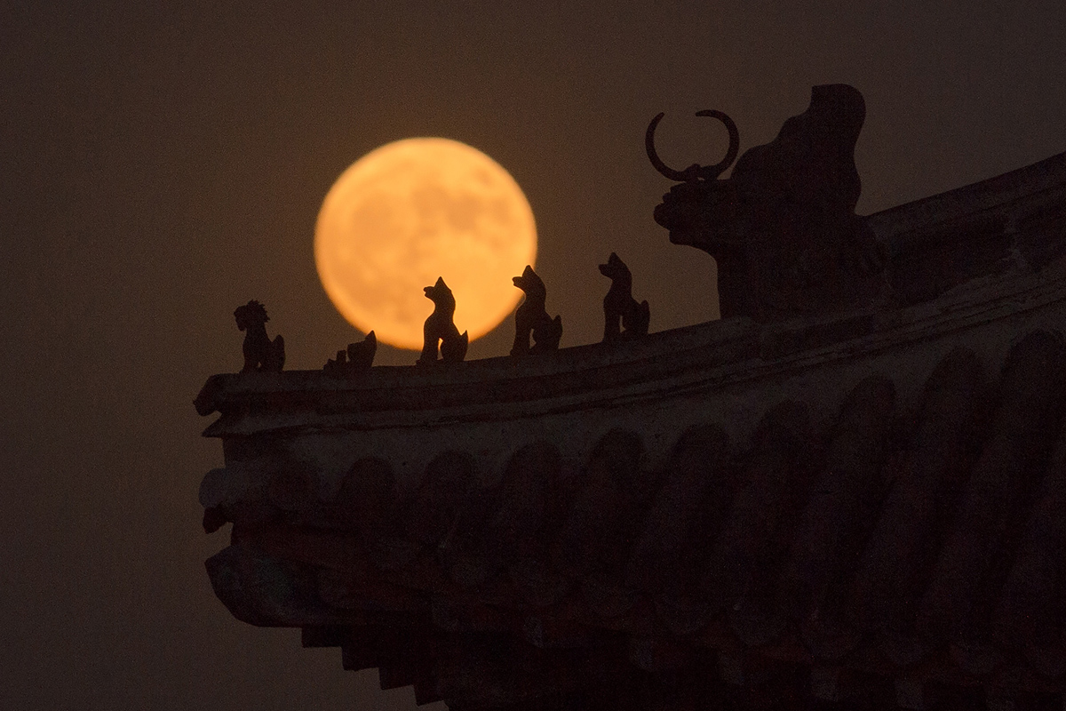 "A ""supermoon"" rises behind small sculptures standing on the roof of a tower in the Forbidden City in Beijing on November 14, 2016. Skygazers headed to high-rise buildings, ancient forts and beaches on November 14 to witness the closest ""supermoon"" to Earth in almost seven decades, hoping for dramatic photos and spectacular surf. The moon will be the closest to Earth since 1948 at a distance of 356,509 kilometres (221,524 miles), creating what NASA described as ""an extra-supermoon"". / AFP / NICOLAS ASFOURI (Photo credit should read NICOLAS ASFOURI/AFP/Getty Images)"